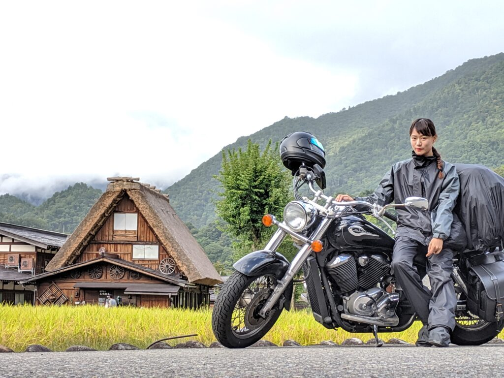 白川郷を背景にバイクにまたがる筆者