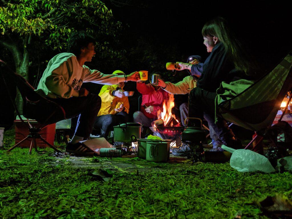 キャンプ場で出会った人々と乾杯する筆者