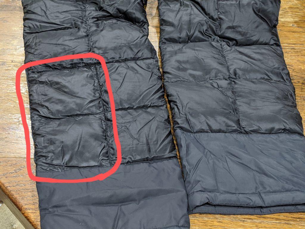 ダウンパンツの修理箇所を赤枠で囲っている