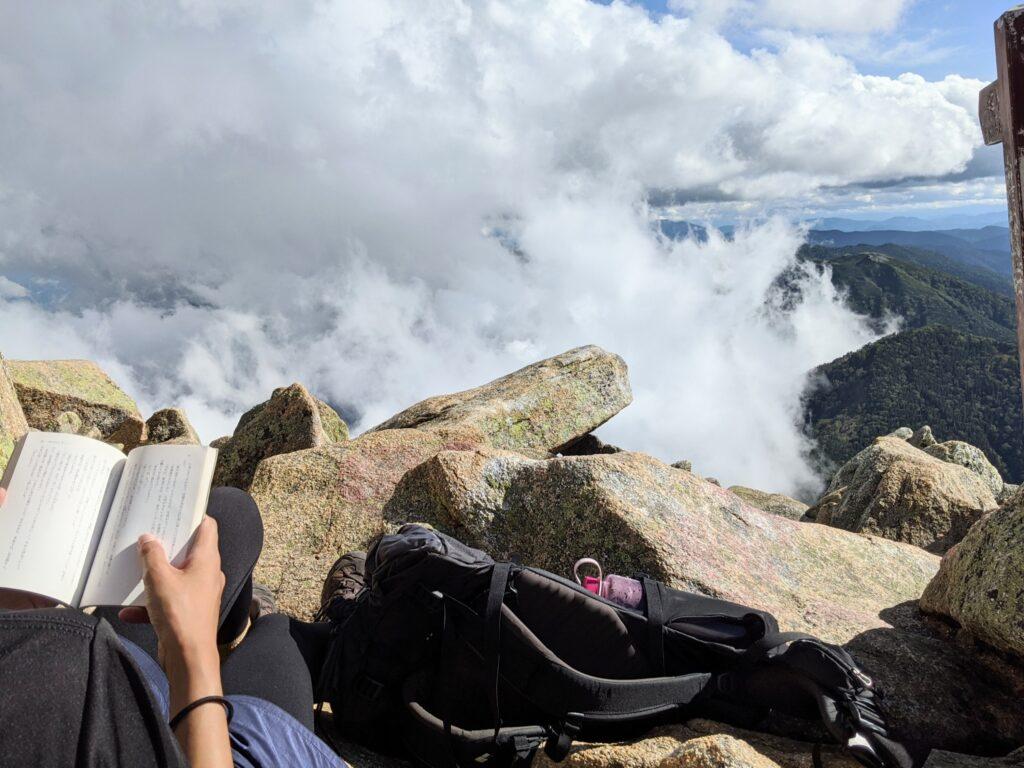 山頂で読書をする筆者