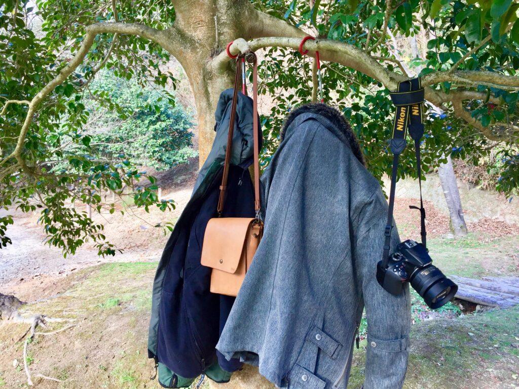 ランタンハンガーで木に上着やカバンをかけている図